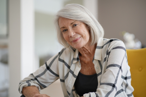 woman smiling while sitting on chair at home