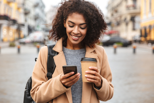 woman holding cup of coffee while looking at her cell phone