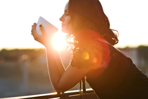 Woman staring at cup outside
